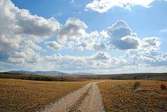 Γήινος δρόμος, μπλε ουρανός και σύννεφα Στοκ Φωτογραφία
