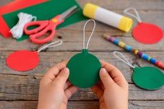 Γίνοντες παιδί κόκκινες και πράσινες σφαίρες Χριστουγέννων από το έγγραφο χαρτονιού Το παιδί κρατά τη σφαίρα Χριστουγέννων στα χέ Στοκ φωτογραφίες με δικαίωμα ελεύθερης χρήσης
