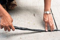 Γαλάκτωμα πίσσας χρήσης εργαζομένων για να εφαρμόσει την ένωση του δρόμου στοκ εικόνα