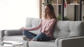 Γαλήνια ήρεμη συνεδρίαση κοριτσιών στον καναπέ που κάνει την άσκηση αναπνοής γιόγκας απόθεμα βίντεο