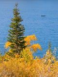 Γαλήνια σκηνή φθινοπώρου με το αλιευτικό σκάφος σε μια λίμνη βουνών στοκ εικόνα