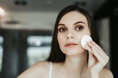 Γαλήνιο αρκετά νέο γυναικείο καθαρίζοντας πρόσωπο εσωτερικό στοκ εικόνες με δικαίωμα ελεύθερης χρήσης
