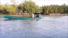 Γαλαζοπράσινη παραδοσιακή ταϊλανδική ξύλινη βάρκα μηχανών, το μήκος σε πόδηα που επιδεικνύει πώς οι άνθρωποι το χρησιμοποιούν ως  φιλμ μικρού μήκους