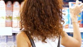 Γαλακτοκομείο αγοράς κοριτσιών στην πίσω άποψη υπεραγορών φιλμ μικρού μήκους