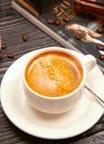Γαλακτώδες cappuchino αφρού στο άσπρο φλυτζάνι που διακοσμείται με τα φασόλια καφέ και τα περιοδικά στοκ εικόνα