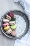 Γαλλικά macarons των διαφορετικών χρωμάτων που εξυπηρετούνται σε ένα μεταλλικό ασημένιο πιάτο στοκ εικόνες