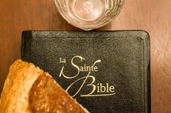 Γαλλική ιερή Βίβλος με το ποτήρι του νερού και τη φραντζόλα του ψωμιού Στοκ Εικόνες