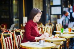 Γαλλικός καφές κατανάλωσης γυναικών στον υπαίθριο καφέ στο Παρίσι, Γαλλία στοκ εικόνες με δικαίωμα ελεύθερης χρήσης