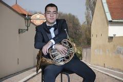 Γαλλικός φορέας κέρατων Παίζοντας πορτρέτο μουσικής ορχηστρών ορείχαλκου Hornist στο υπόβαθρο της πόλης στοκ φωτογραφίες με δικαίωμα ελεύθερης χρήσης