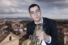 Γαλλικός φορέας κέρατων Όργανο μουσικής ορχηστρών ορείχαλκου παιχνιδιού Hornist Πορτρέτο στο υπόβαθρο της πόλης στοκ εικόνα με δικαίωμα ελεύθερης χρήσης