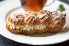 Γαλλικό γλυκό ECLAIR στο πιάτο στον πίνακα στοκ φωτογραφία