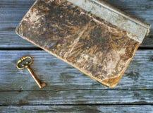 Γαλλικό κλειδί χαλκού και αρχαίο βιβλίο που βρίσκονται σε έναν πίνακα των παλαιών πινάκων στοκ εικόνα με δικαίωμα ελεύθερης χρήσης