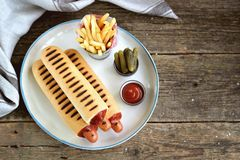 Γαλλικό χοτ-ντογκ με το κέτσαπ, τη μουστάρδα, τη μαγιονέζα και το μαριναρισμένο αγγούρι Στοκ εικόνα με δικαίωμα ελεύθερης χρήσης