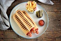 Γαλλικό χοτ-ντογκ με το κέτσαπ, τη μουστάρδα, τη μαγιονέζα και το μαριναρισμένο αγγούρι Στοκ εικόνες με δικαίωμα ελεύθερης χρήσης