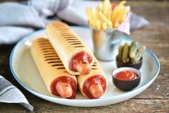 Γαλλικό χοτ-ντογκ με το κέτσαπ, τη μουστάρδα, τη μαγιονέζα και το μαριναρισμένο αγγούρι Στοκ Φωτογραφίες
