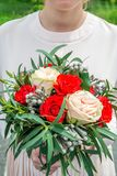 Γαμήλια άσπρος-κόκκινη ανθοδέσμη στα χέρια της νύφης στοκ εικόνες