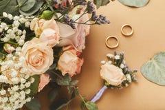 Γαμήλια ανθοδέσμη και χρυσά δαχτυλίδια, κινηματογράφηση σε πρώτο πλάνο Στοκ Φωτογραφίες