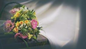 Γαμήλια ανθοδέσμη με τα τριαντάφυλλα σε έναν ξύλινο πάγκο στοκ φωτογραφία