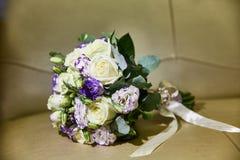 Γαμήλια ανθοδέσμη με τις κορδέλλες Τριαντάφυλλα, freesia Μπεζ υπόβαθρο στοκ φωτογραφία