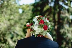 Γαμήλια ανθοδέσμη στα χέρια πίσω από την πίσω Στοκ Εικόνα