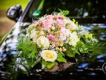Γαμήλια ανθοδέσμη στην κουκούλα ενός μαύρου αναδρομικού αυτοκινήτου Στοκ εικόνες με δικαίωμα ελεύθερης χρήσης