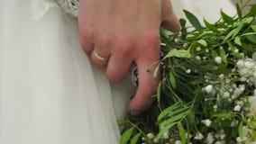 Γαμήλια ανθοδέσμη της Νίκαιας στο χέρι νυφών ` s συνδετήρας Fiancee σε ένα όμορφο άσπρο φόρεμα που κρατά μια όμορφη ανθοδέσμη του φιλμ μικρού μήκους