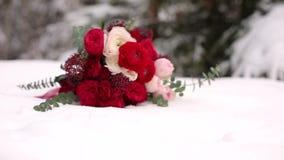Γαμήλια ανθοδέσμη των κόκκινων και άσπρων λουλουδιών στο χιόνι στα αειθαλή conferous ξύλα Κλείστε και μακρο άποψη των τρυφερών τρ φιλμ μικρού μήκους