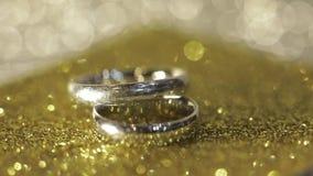 Γαμήλια ασημένια δαχτυλίδια που βρίσκονται στη λαμπρή στιλπνή επιφάνεια Να λάμψει με το φως Κινηματογράφηση σε πρώτο πλάνο απόθεμα βίντεο