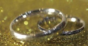 Γαμήλια ασημένια δαχτυλίδια που βρίσκονται στη λαμπρή στιλπνή επιφάνεια Να λάμψει με το φως Κινηματογράφηση σε πρώτο πλάνο φιλμ μικρού μήκους