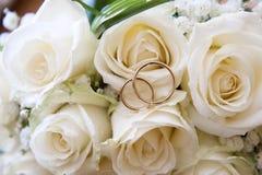Γαμήλια δαχτυλίδια σε μια ανθοδέσμη των τριαντάφυλλων Στοκ Φωτογραφίες