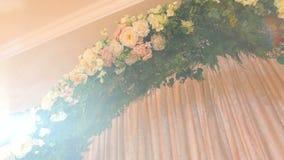 Γαμήλια αψίδα με τα λουλούδια και το φωτεινό φως του ήλιου απόθεμα βίντεο