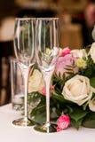 Γαμήλια γυαλιά στον πίνακα άσπρα και ρόδινα τριαντάφυλλα στο υπόβαθρο κλείστε επάνω Στοκ Εικόνα