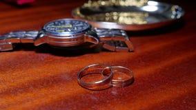 Γαμήλια δαχτυλίδια και ένα άτομο ` s wristwatch στον πίνακα απόθεμα βίντεο