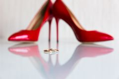 Γαμήλια δαχτυλίδια και βαλμένα τακούνια παπούτσια στοκ εικόνα με δικαίωμα ελεύθερης χρήσης