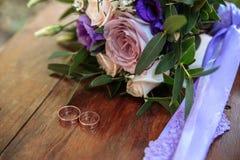 Γαμήλια δαχτυλίδια και ιώδης ανθοδέσμη στην ξύλινη επιφάνεια Στοκ εικόνες με δικαίωμα ελεύθερης χρήσης
