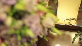 Γαμήλια δαχτυλίδια με μια ανθοδέσμη των λουλουδιών απόθεμα βίντεο