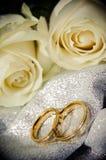 Γαμήλια δαχτυλίδια με τα άσπρα τριαντάφυλλα στοκ εικόνες