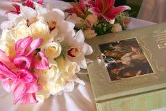 Γαμήλια δαχτυλίδια με τη Βίβλο και τα λουλούδια Στοκ Εικόνες