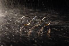 Γαμήλια δαχτυλίδια που βρίσκονται στη σκοτεινή επιφάνεια που λάμπει με το φως Παφλασμοί νερού Βροχή στοκ εικόνα