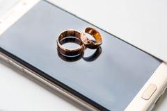 Γαμήλια δαχτυλίδια σε ένα κινητό τηλέφωνο Στοκ φωτογραφία με δικαίωμα ελεύθερης χρήσης