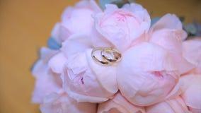 Γαμήλια δαχτυλίδια σε μια ανθοδέσμη των άσπρων λουλουδιών Γαμήλια δαχτυλίδια και ανθοδέσμη του σκούρο μπλε λουλουδιού κλείστε επά Στοκ Φωτογραφία