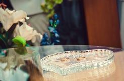 Γαμήλια δαχτυλίδια σε μια στάση γυαλιού στο γραφείο ληξιαρχείων στοκ εικόνες
