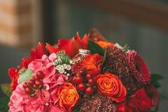 Γαμήλια δαχτυλίδια στη φωτεινή κόκκινη γαμήλια ανθοδέσμη με τα πορτοκαλιά, πορφυρά και τριαντάφυλλα του Μπορντώ, την παπαρούνα κα Στοκ Φωτογραφίες