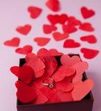 Γαμήλια δαχτυλίδια στις κόκκινες καρδιές Ρόδινη ανασκόπηση Η έννοια του αρραβώνα, διαζύγιο, χωρισμός, απιστία Εκλεκτική εστίαση στοκ φωτογραφία με δικαίωμα ελεύθερης χρήσης