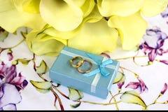 Γαμήλια δαχτυλίδια στον πίνακα και μια ανθοδέσμη των λουλουδιών στοκ εικόνες