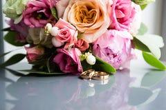 Γαμήλια δαχτυλίδια στο υπόβαθρο μιας ανθοδέσμης των λουλουδιών στοκ εικόνες