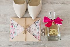 Γαμήλια εξαρτήματα: νυφικά παπούτσια, δαχτυλίδια, πρόσκληση, άρωμα Γαμήλιες λεπτομέρειες στις μπεζ σκιές Στοκ εικόνα με δικαίωμα ελεύθερης χρήσης
