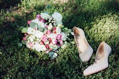 Γαμήλια εξαρτήματα: παπούτσια και ανθοδέσμη νυφών ` s Όμορφη γαμήλια ανθοδέσμη των μικρών τριαντάφυλλων Στοκ Φωτογραφία