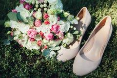 Γαμήλια εξαρτήματα: παπούτσια και ανθοδέσμη νυφών ` s Όμορφη γαμήλια ανθοδέσμη των μικρών τριαντάφυλλων Στοκ φωτογραφία με δικαίωμα ελεύθερης χρήσης