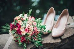Γαμήλια εξαρτήματα: παπούτσια και ανθοδέσμη νυφών ` s Όμορφη γαμήλια ανθοδέσμη των μικρών τριαντάφυλλων Στοκ εικόνες με δικαίωμα ελεύθερης χρήσης